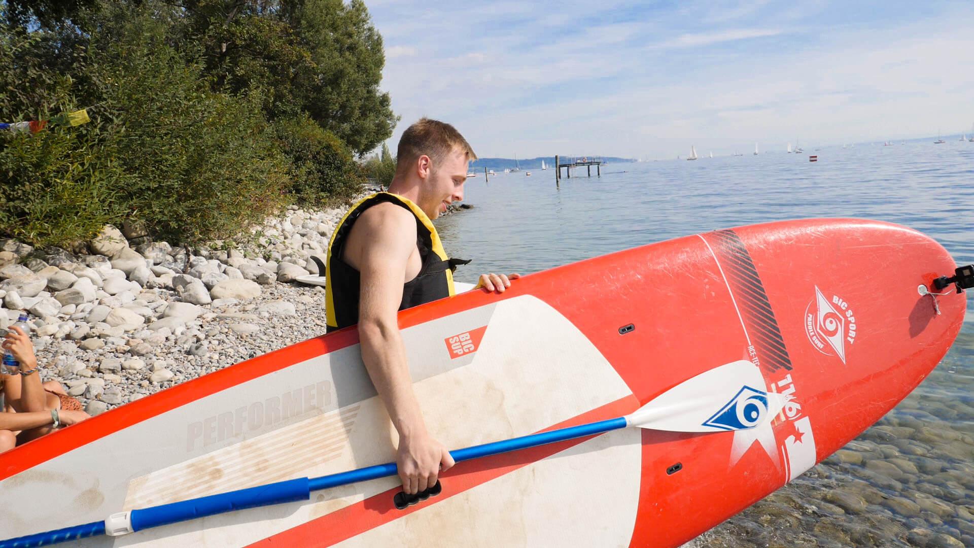 Markus der mit einem Surfbrett gerade in den Bodensee geht